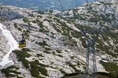 Фуникулер к горе Dachstein в зоне Salzkammergut Австралии нейтральные цветы Серые горы на заднем плане и insi людей стоковая фотография