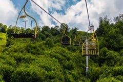 Фуникулер с кабинами для 3 мест и желтых перил против фона сочных зеленых деревьев Стоковая Фотография RF