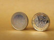 1 фунт и 1 монетка евро над бумажной предпосылкой Стоковые Изображения