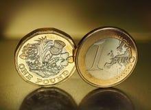 1 фунт и 1 монетка евро над предпосылкой металла Стоковые Изображения
