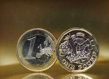 1 фунт и 1 монетка евро над предпосылкой металла Стоковые Фотографии RF