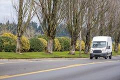 Фургон небольшого компактного коммерчески транспорта мини управляя на прямой местной дороге стоковые изображения rf