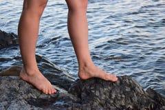 2 фута ` s женщин стоят на больших камнях около воды Стоковая Фотография