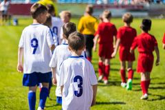 Футболисты детей входя в тангаж после рефери в 2 строки Футбольные команды молодости начиная спичку турнира стоковое изображение rf