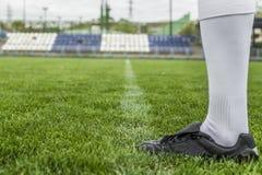 Футболист в ботинках на футбольном стадионе Стоковое фото RF