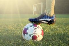 Футболист в действии с футболом в ярко освещенном внешнем стадионе Фокус на переднем плане и футбольный мяч с малой глубиной  стоковые изображения