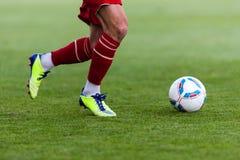 Футболист пинает шарик Стоковая Фотография