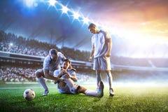 Футболист помогает onother одному на панораме предпосылки стадиона захода солнца Стоковое Изображение