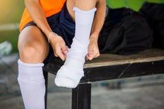 Футболист сидящ и кладущ белый носок спорта стоковые изображения