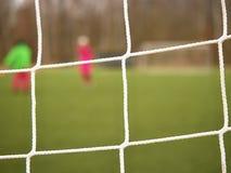 Футболист стоит против цели с сетью и стадионом Сеть строба футбола Строб футбола Стоковое Изображение