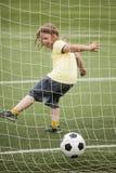 Футболист футбола бега ребенка Мальчик с шариком на зеленой траве стоковое изображение
