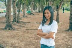 Футболка, она стоя на зеленой траве в парке и усмехаться женщины нося белая стоковое изображение rf