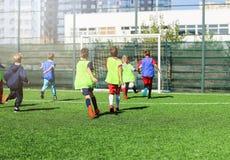 Футбольная команда - мальчики в красном и голубом, зеленом равномерном футболе игры на зеленом поле Игра команды, тренировка, акт стоковое фото rf