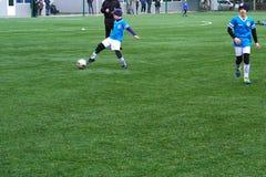 Футбольная команда ` s детей на тангаже Учебный полигон футбола детей Молодые футболисты бежать после шарика стоковые изображения