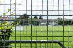 Футбольное поле футбола увиденное через железный строб загородки Стоковая Фотография RF