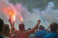 Футбольные болельщики идут к стадиону и горят фейерверки стоковые фотографии rf