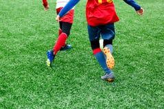 Футбольные команды - мальчики в красном, голубом, белом равномерном футболе игры на зеленом поле мальчики капая капая навыки стоковое изображение