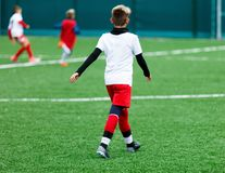 Футбольные команды - мальчики в красном, голубом, белом равномерном футболе игры на зеленом поле мальчики капая капая навыки стоковые фото