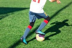 Футбольные команды - мальчики в красном, голубом, белом футболе игры sportswear на зеленом поле мальчики капая капая навыки Игра  стоковые фотографии rf