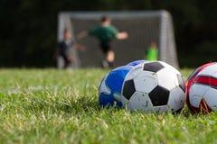 Футбольные мячи на зеленом поле с игроками в предпосылке стоковые фотографии rf