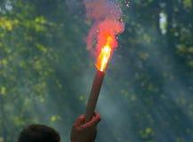 Футбольный болельщик держит горящий фейерверк стоковая фотография rf