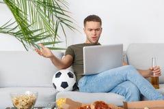 Футбольный матч болельщика молодого человека наблюдая на раздражанной компьтер-книжке Стоковая Фотография RF