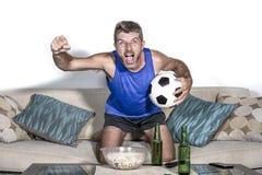 Футбольный матч молодого привлекательного человека счастливый и excited смотря на ТВ празднуя цель победы шальную и спастическую  стоковая фотография