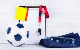 Футбольный мяч, бутылка воды на шортах спорт, и свисток, карточки штрафа и таблетка для записывать судьи, backgr стоковые изображения