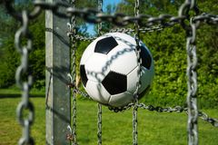 Футбольный мяч в цели с цепями и зеленой естественной предпосылкой стоковые изображения