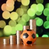 Футбольный мяч и стога золотых монеток в диаграмме роста на запачканной предпосылке bokeh стоковые изображения rf