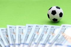 Футбольный мяч на зеленом поле, рядом с счетами 100-доллара США поле глубины отмелое Деньги концепции и футбол, pr Стоковое Изображение RF