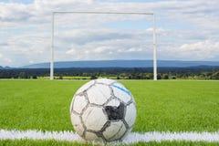 Футбольный мяч на решетке искусственного зеленого цвета футбольного поля дерновины белой с backgound неба Стоковое Изображение