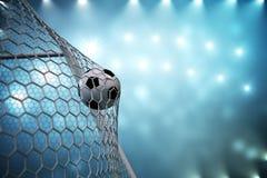 футбольный мяч перевода 3d в цели Футбольный мяч в сети с предпосылкой фары и стадиона светлой, концепцией успеха Стоковое Изображение