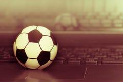 Футбольный мяч сувенира на клавиатуре компьтер-книжки Концепция футбольного матча Стоковое Фото