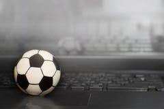Футбольный мяч сувенира на клавиатуре компьтер-книжки Концепция футбольного матча Стоковое Изображение