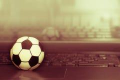 Футбольный мяч сувенира на клавиатуре компьтер-книжки Концепция футбольного матча Стоковые Фото