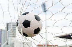 Футбол футбола в сети цели с полем неба Стоковые Изображения RF