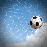 Футбол футбола в сети цели с полем неба Стоковое фото RF