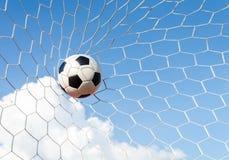 Футбол футбола в сети цели с полем неба Стоковое Изображение RF