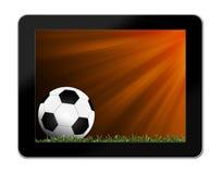 Футбол в зеленой траве с предпосылкой в таблетк-ПК Стоковые Фото