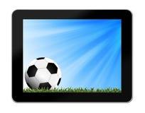 Футбол в зеленой траве с предпосылкой в таблетк-ПК Стоковое Изображение