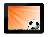 Футбол в зеленой траве с предпосылкой в таблетк-ПК Стоковое фото RF