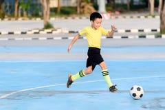 Футбол игры мальчика на голубом конкретном поле стоковое изображение rf