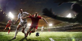 Футболисты в действии на панораме предпосылки стадиона захода солнца