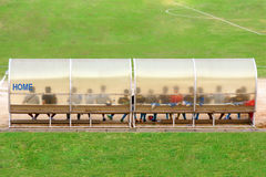 Футболисты и штат сидят на стенде около футбольного поля (Хозяин поля) Стоковая Фотография RF