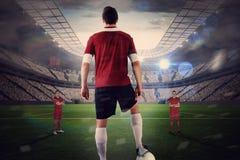 Футболист в красном цвете при шарик смотря на оппозицию Стоковое фото RF