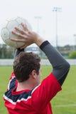 Футболист в красный бросать от боковой линии Стоковое Изображение