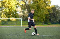 Футболист играя с шариком на футбольном поле стоковое изображение rf