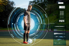 Футболист играя с шариком на футбольном поле Стоковое Изображение