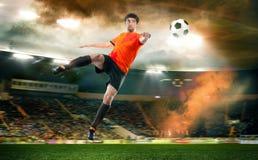 Футболист поражая шарик на стадионе стоковые фото